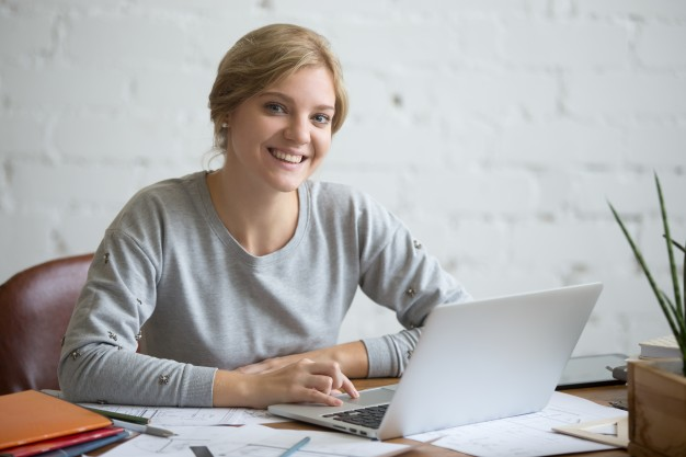 portrait-of-a-smiling-student-girl-at-desk-with-laptop_1163-2565